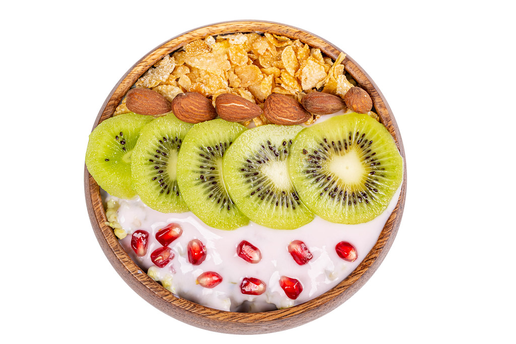 Cornflakes with almonds, kiwi, pomegranate and yogurt, top view