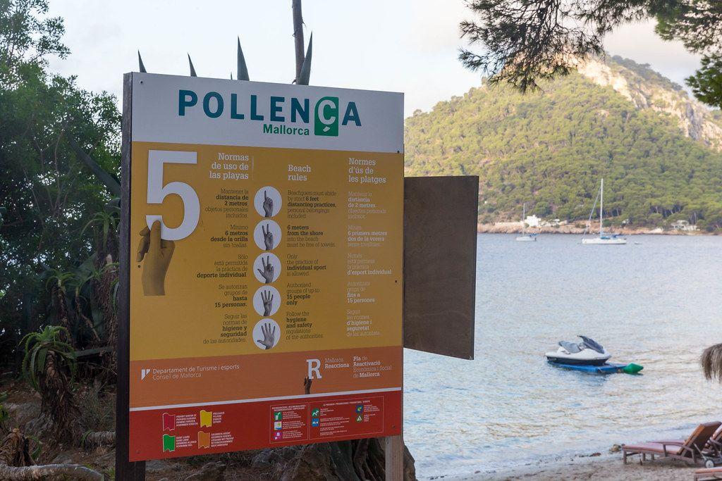 Corona-Abstandregeln am Strand auf Spanisch, Englisch und Katalanisch in Pollença auf Mallorca