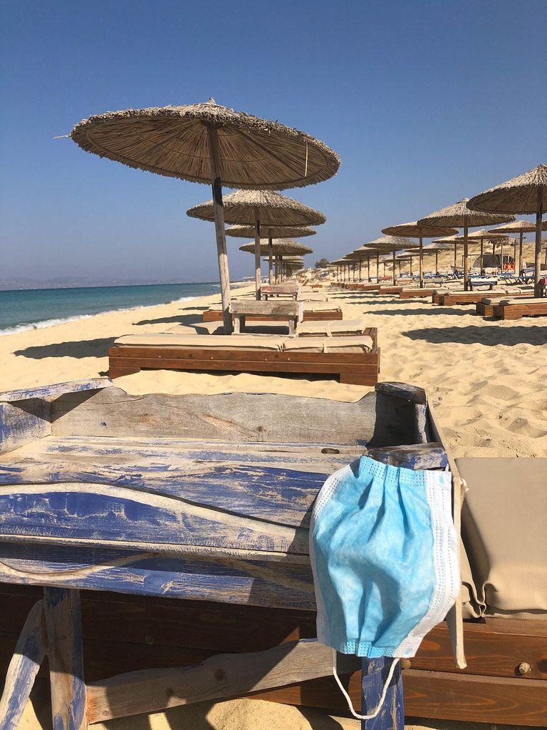 Corona-Maßnahmen im Urlaub: MNS-Maske zum Schutz vor Covid-19 am Sandstrand von Naxos, Griechenland