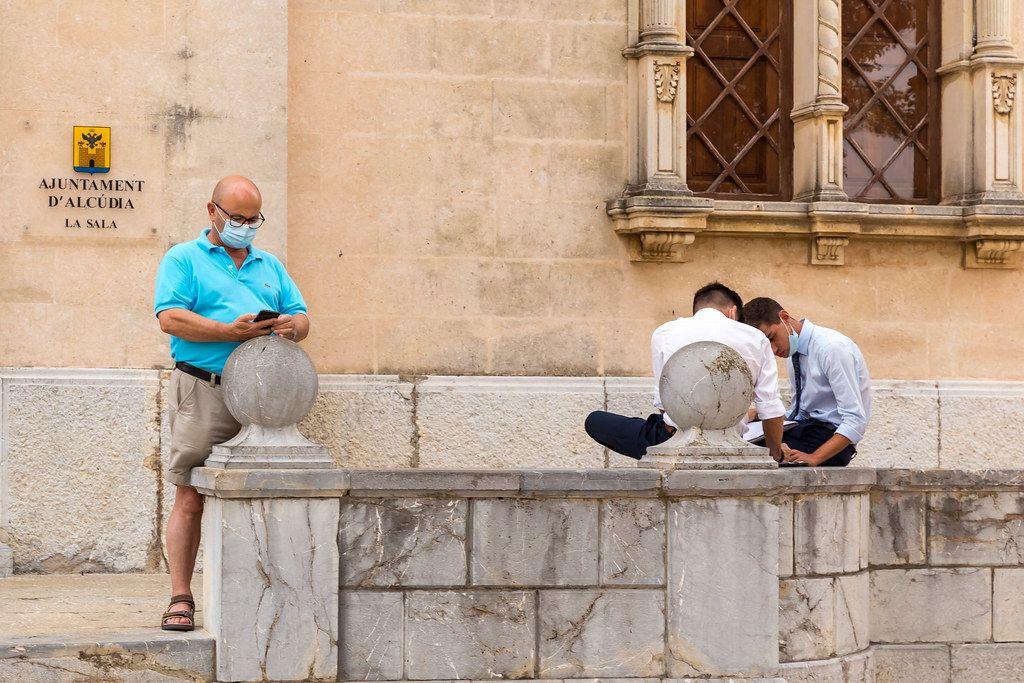 Corona-Maßnahmen in Spanien: drei Männer mit Mundschutz vor dem Rathaus von Alcudía (Mallorca)