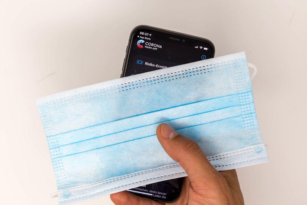 Coronavirus Infektionsschutz: Smartphone mit Corona-Warn-App und OP-Maske in der Hand
