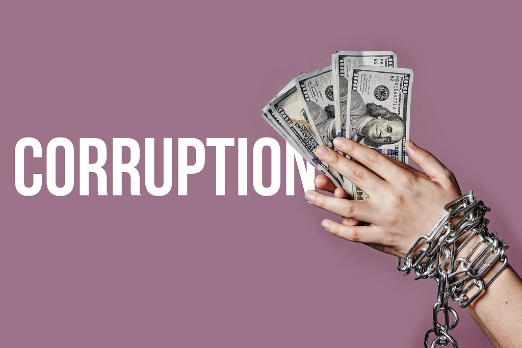 Corruption - Woman hands in steel chains and dollars