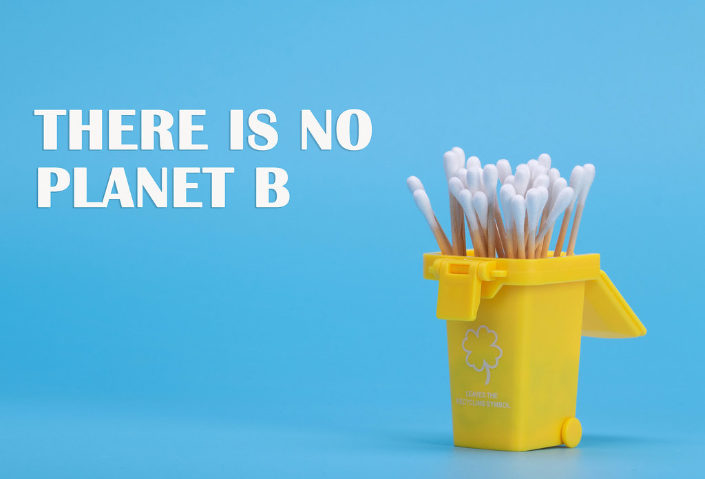 Cotton swabs in a trash can with There is no planet B text