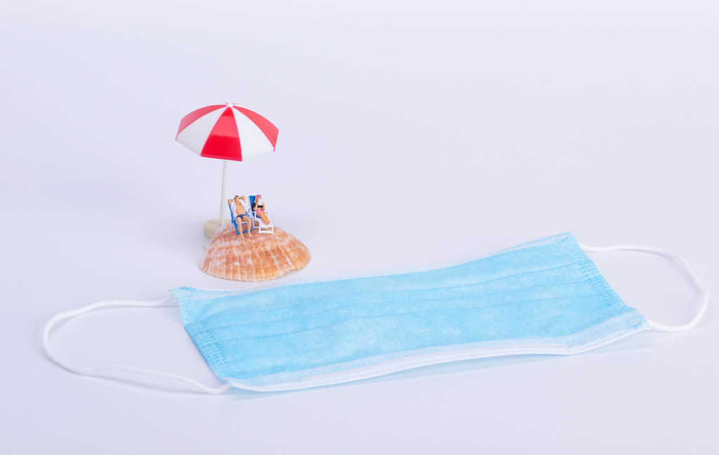 Couple sitting in deck chairs on sea shell and medical face mask
