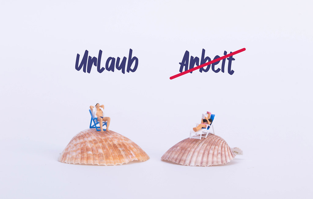 Couple sitting in deck chairs on sea shell with Urlaub and crossed Arbeit text