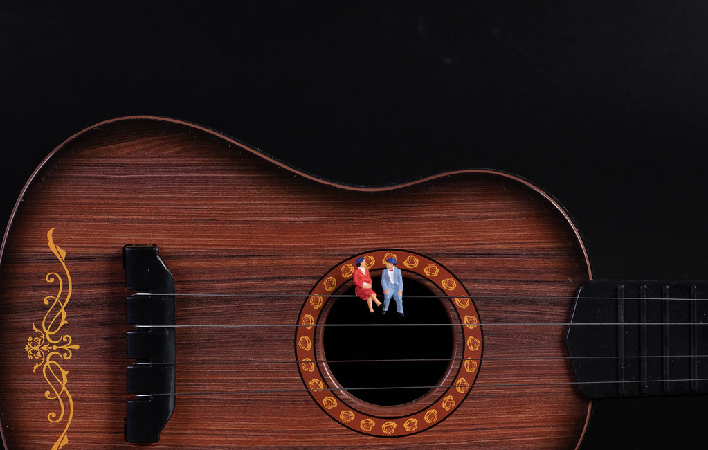 Couple sitting on a guitar with black background