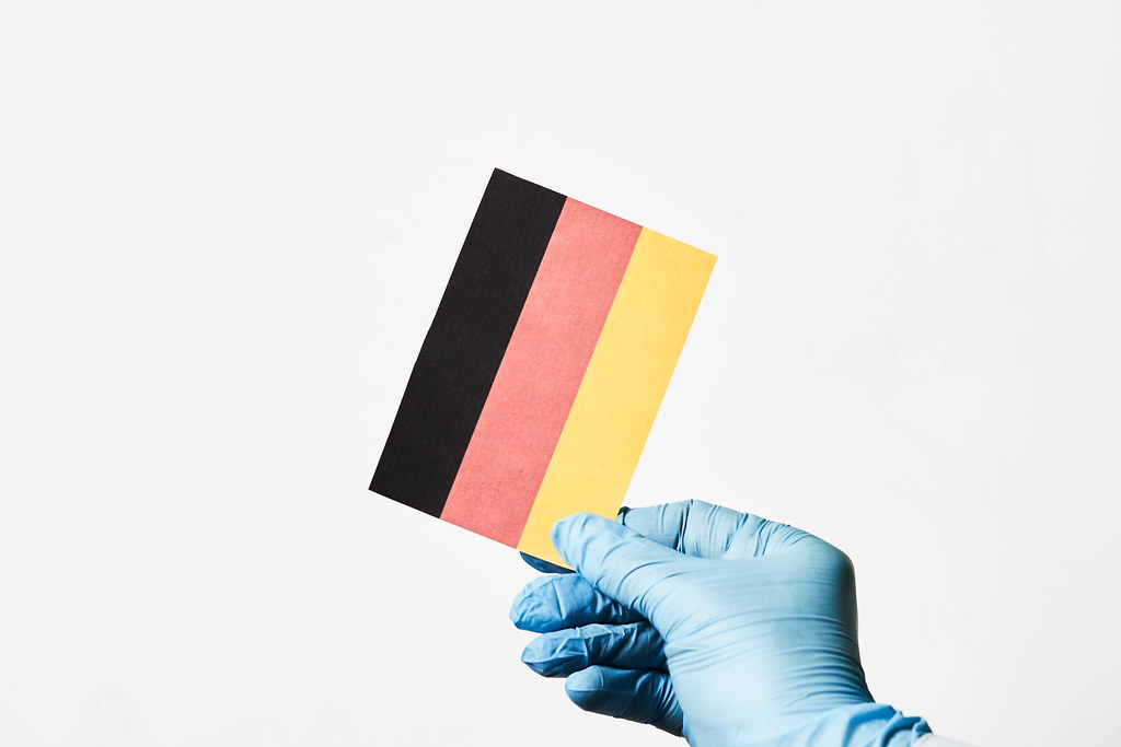 Covid-19 in Deutschland. Hand mit Einmalhandschuh hält eine deutsche Flagge vor weißem Hintergrund
