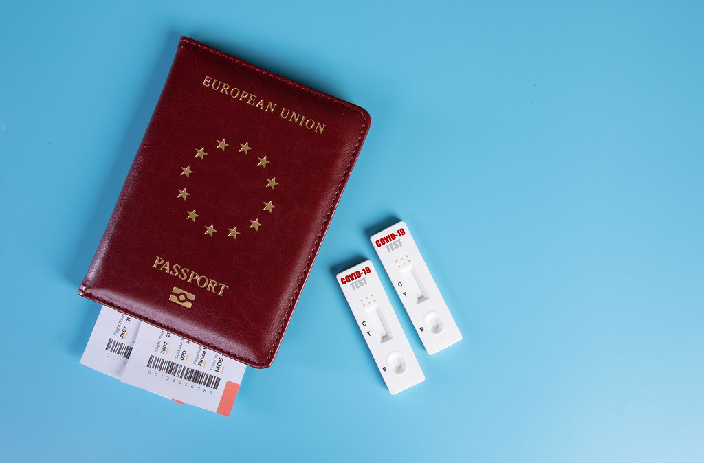 COVID-19 test cassette on passport on blue background
