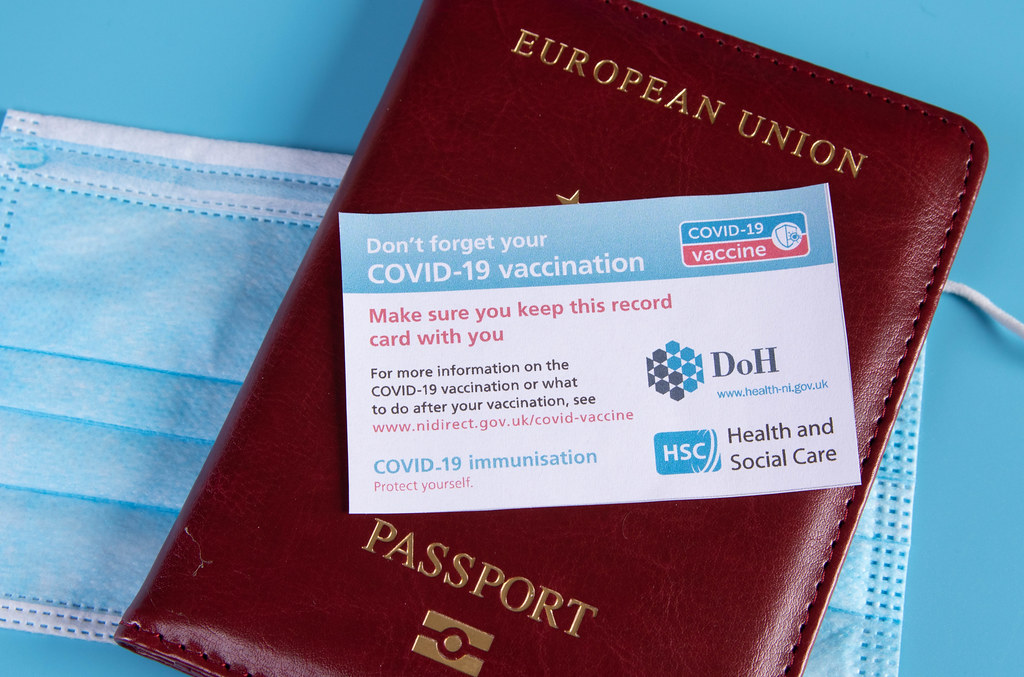Covid-19 vaccination record card with passport and medical face mask