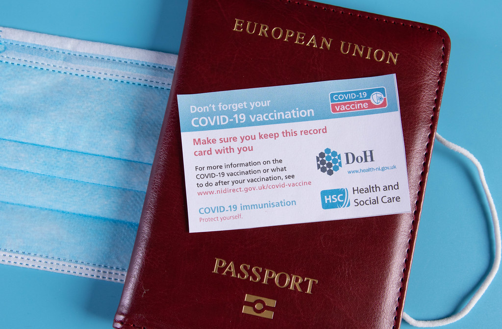 Covid-19 vaccination record card with passport on blue background