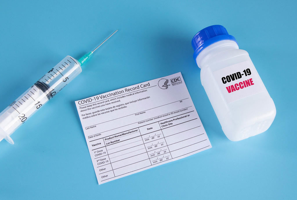 Covid-19 vaccine with syringe and vaccination record card