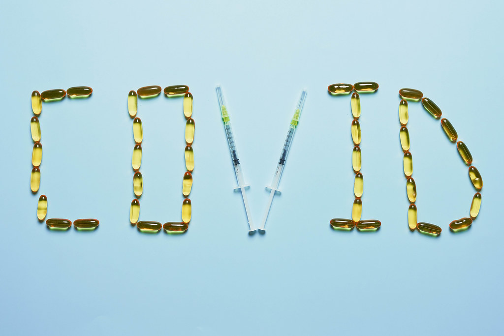 Covid text made with medical pills and syringes