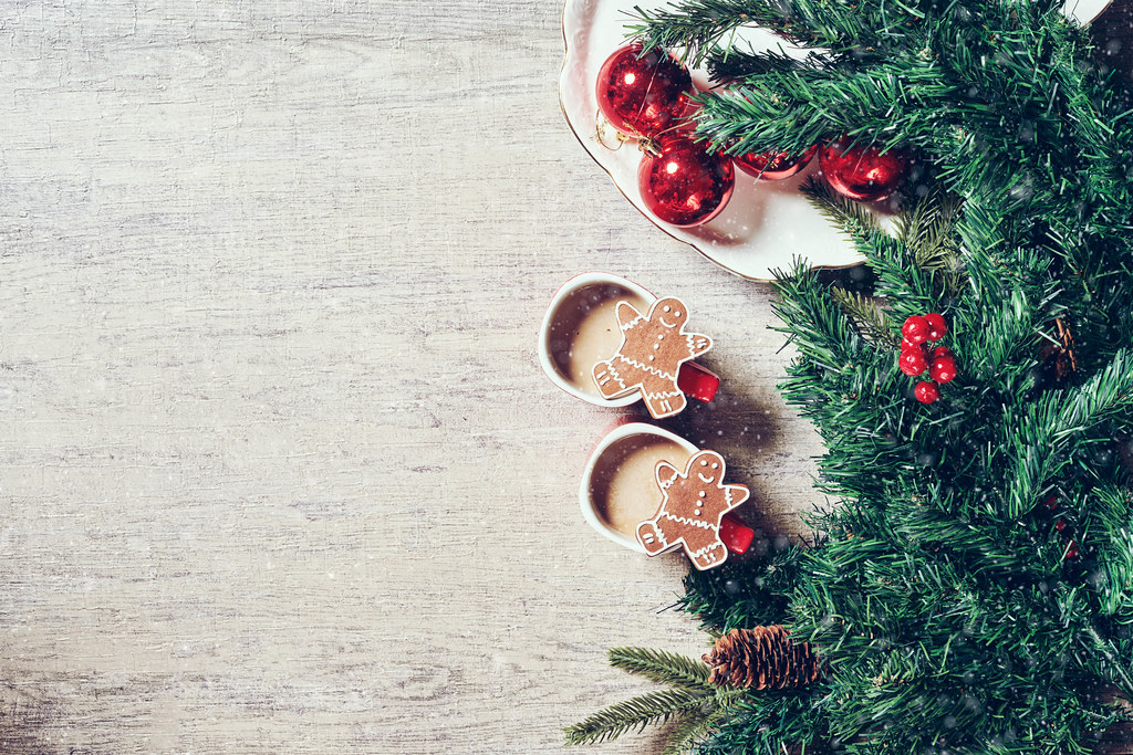 Cozy Christmas background with coffee cup, baked cookies and pine cones on wooden background