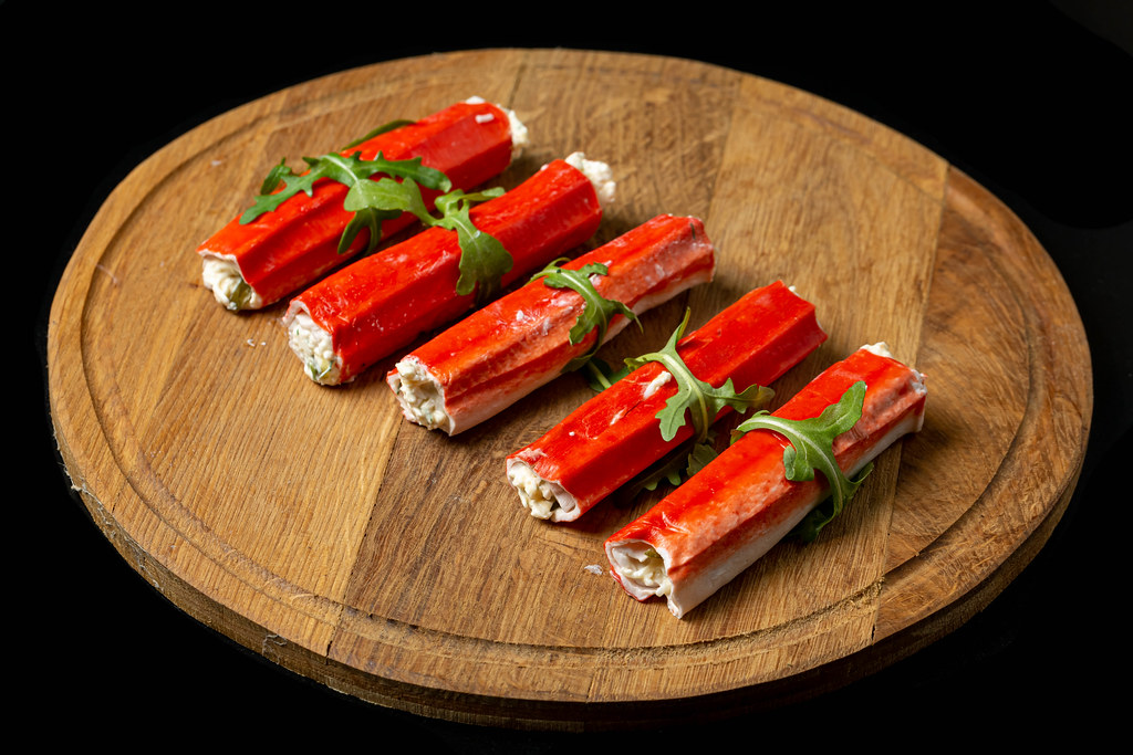 Crab sticks stuffed with cheese and herbs on a wooden round board