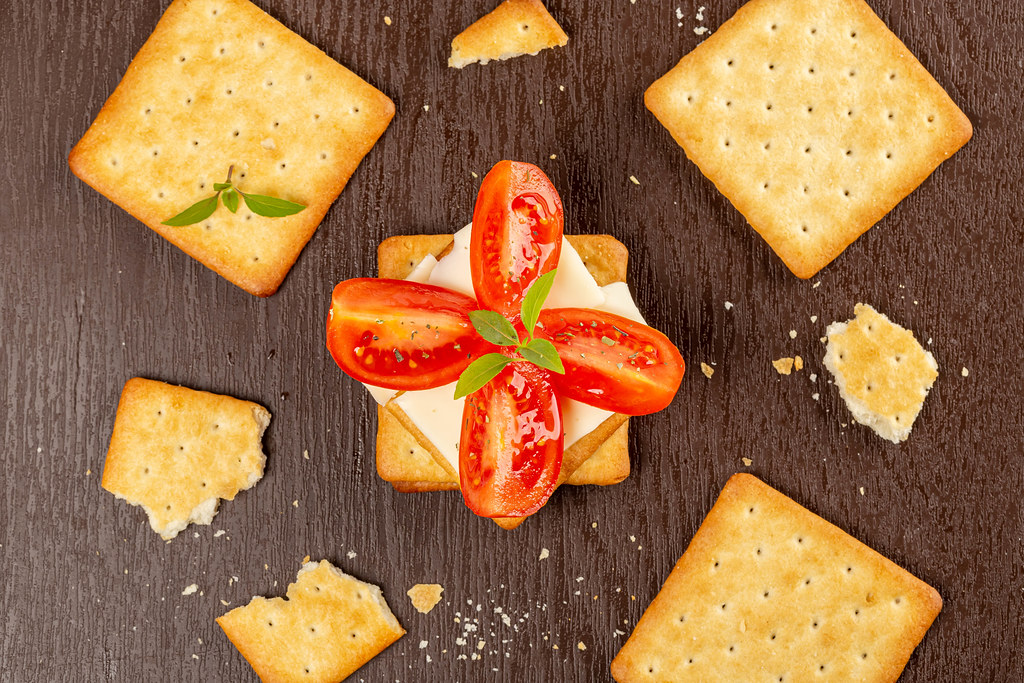 Crackers with cheese, tomato and basil leaves on a brown background