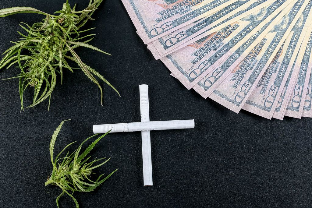 Cross made of cigarettes on a black background with money and hemp