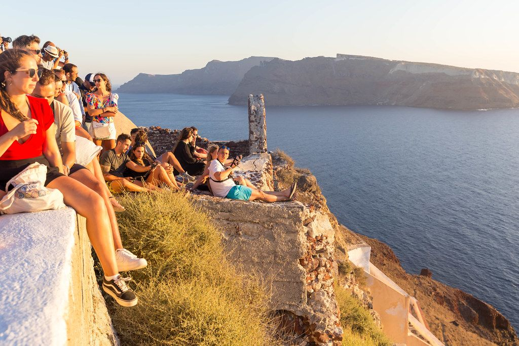 Crowded sunset spot: tourists in Santorini gather at the perfect spot for a sunset photo in Oia