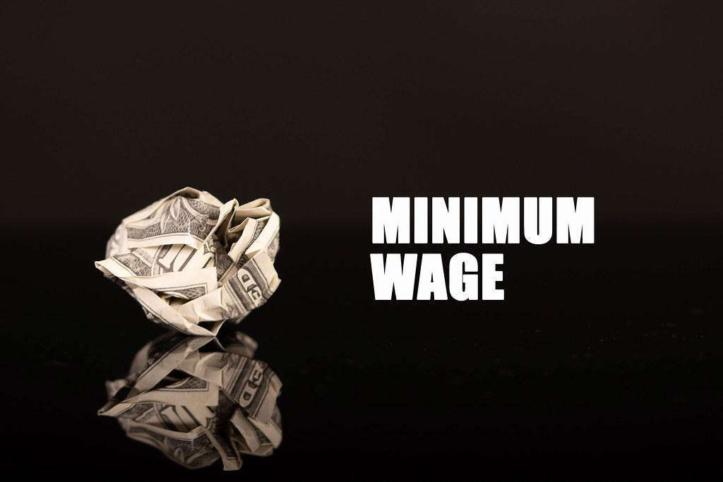 Crumpled money with Minimum wage text