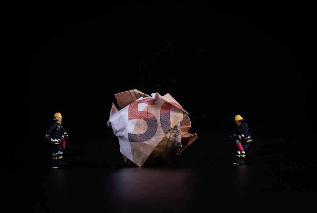 Crushed 50 euro banknote with miniature firefighters on black background