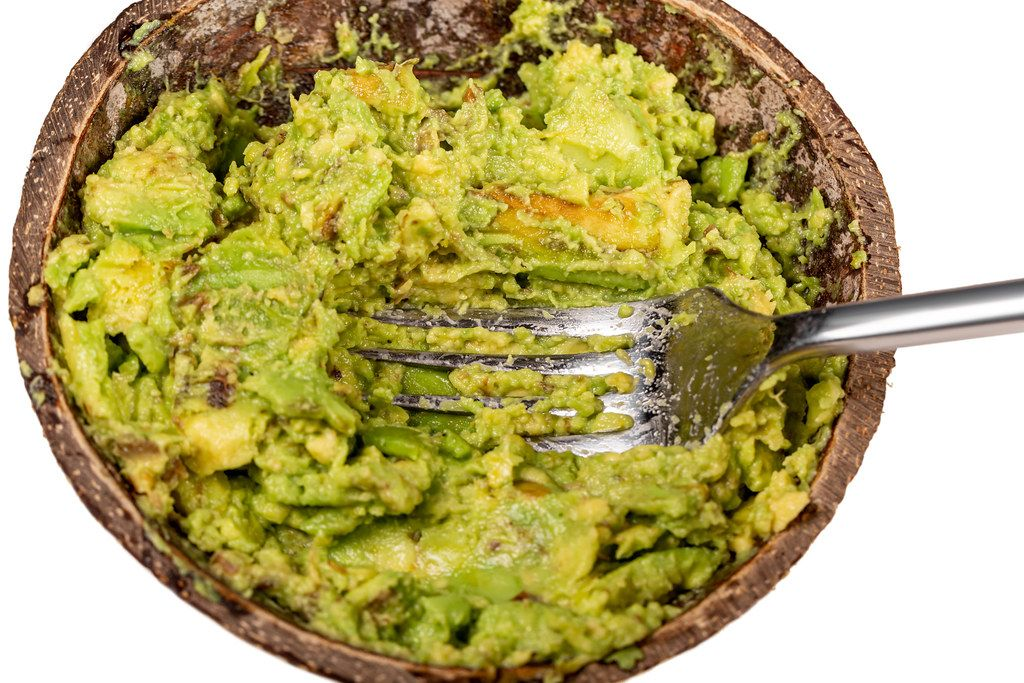 Crushed avocado in a bowl with a fork