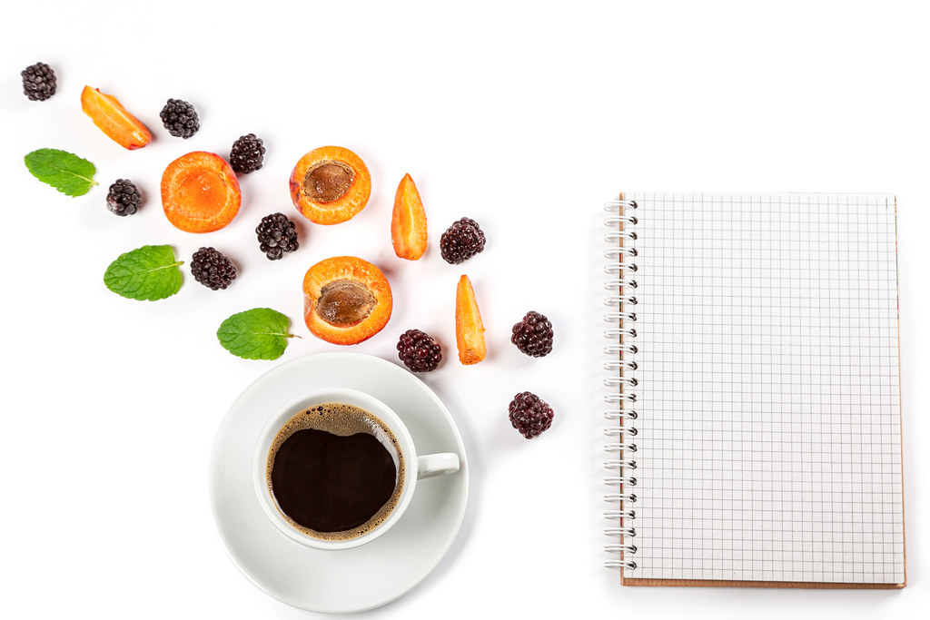 Cup of coffee with berries and mint leaves on white background with notepad, top view