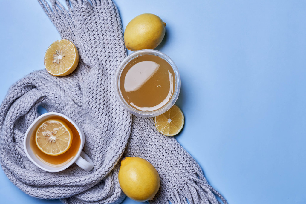 Cup of hot tea with lemon, honey and scarf on blue background