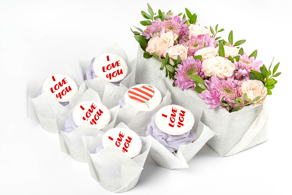 Cupcakes and bouquet of flowers on white background, concept of congratulations on valentine