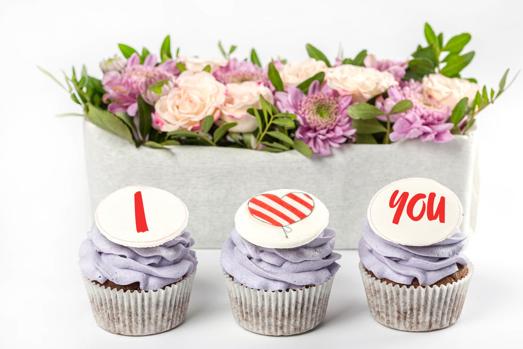 Cupcakes with purple cream and decor i love you on a white background with flowers