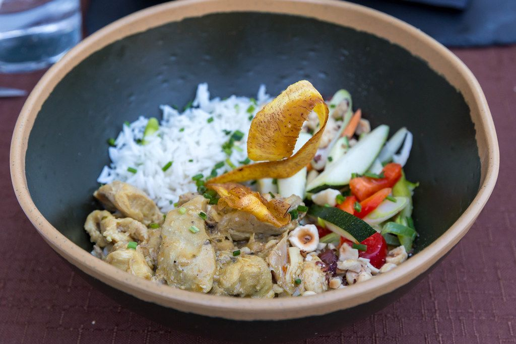 Curry-Landhuhn nach Q11-Art mit Gemüse der Saison und Reis in einem schwarzen Teller bei Q11, Pollença