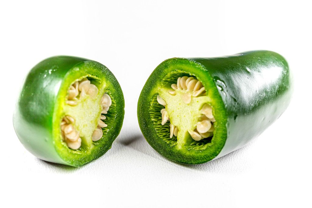 Cut fresh green jalapeno pepper on white background
