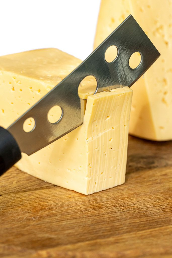 Cutting cheese with a knife, close-up