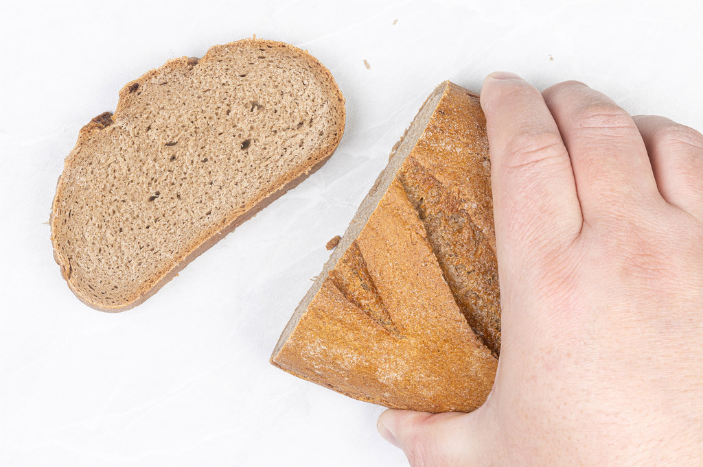 Dark bread with unleavened dough in the hand above table