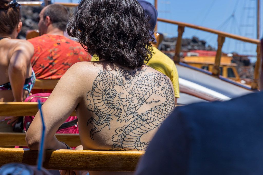 Dark-haired woman with a large dragon tattoo on her naked back