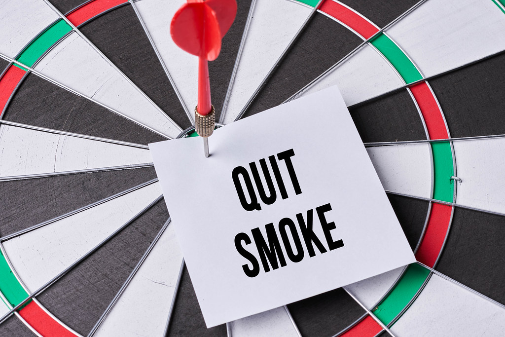 Dart arrow hitting a note on target center of dartboard with text - quit smoke. No smoking, World no tobacco day concept