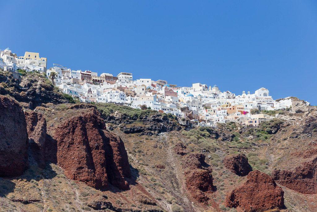 Das berühmte Künstlerdorf Oia auf Santorin mit den drei blauen Kuppeln und vielen weißen Häusern