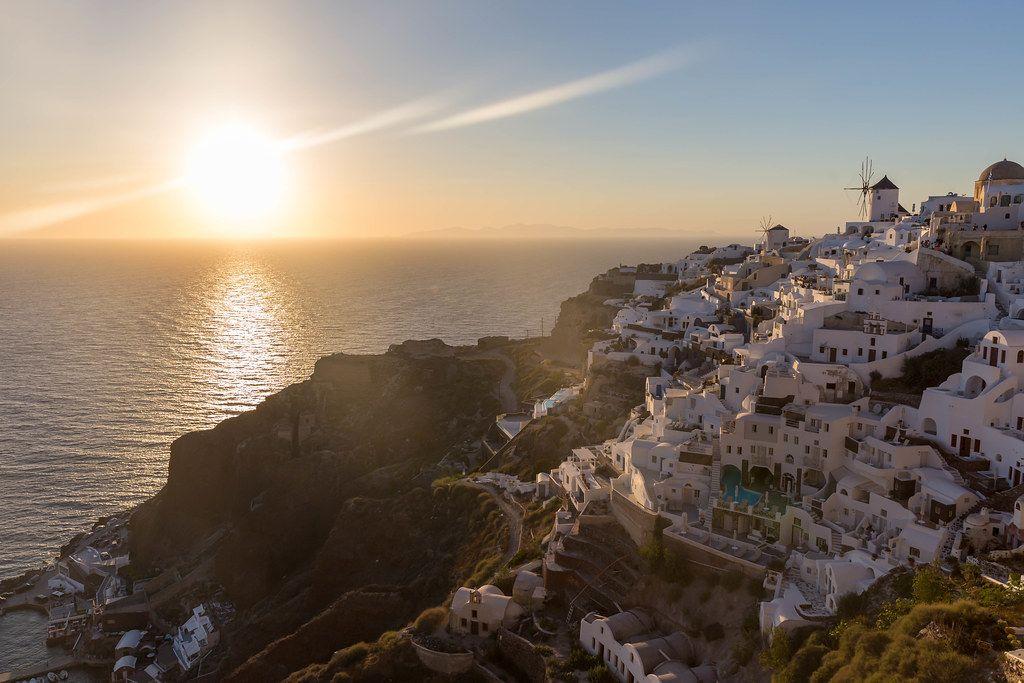 Das malerische Dorf Oia auf Santorin bei Sonnenuntergang. Die Sonne geht im Meer unter