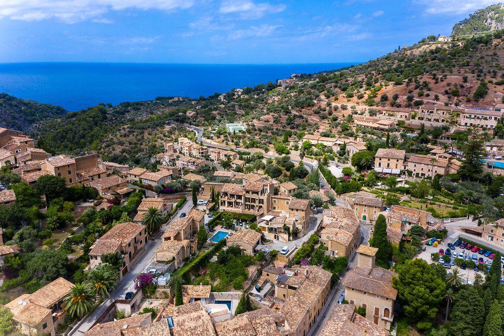 Das Mittelmeer und die Dächer von Deià. Luftbild vom Künstlerdorf an der Westküste Mallorcas