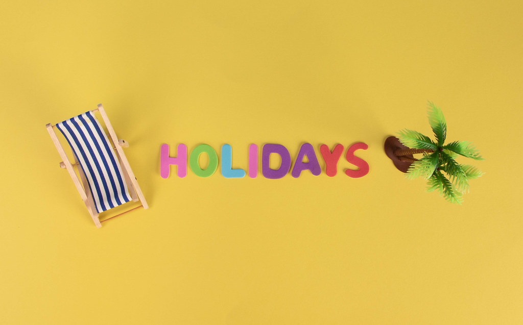 Deck chair and palm tree with Holidays text on yellow background