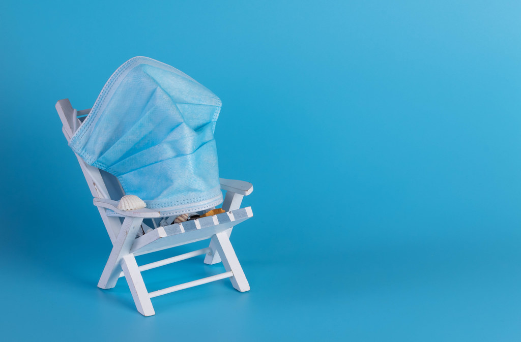 Deckchair with medical face mask on blue background