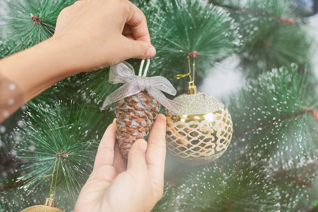 Decorating a Christmas tree with toys and pine cones