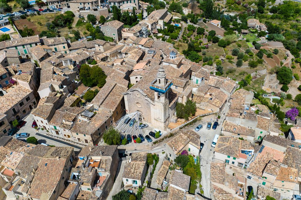 Decorations and cars parked in front of the Sant Bartolomeu church in Valldemossa. Aerial view