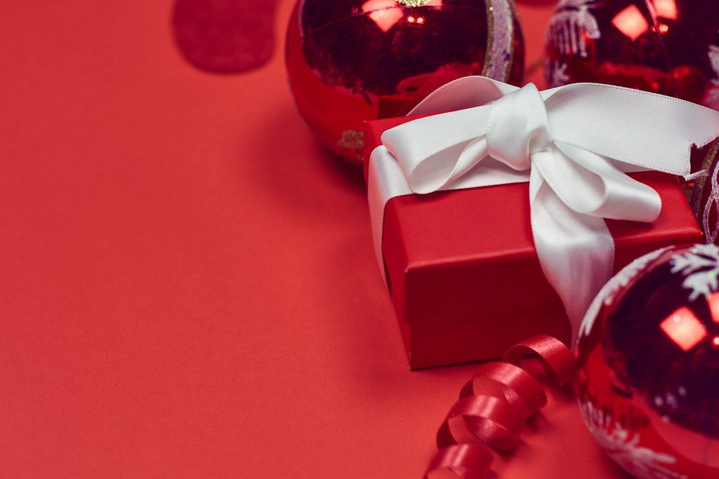 Decorative Christmas toys and gift box on the red background