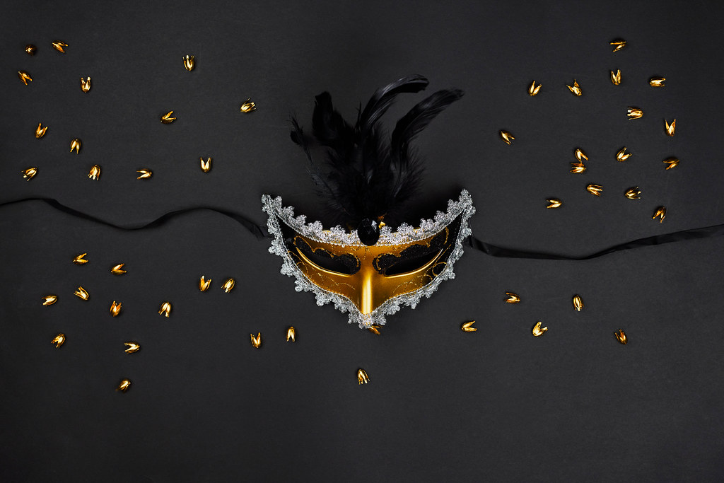 Decorative venetian mask with feathers on black background