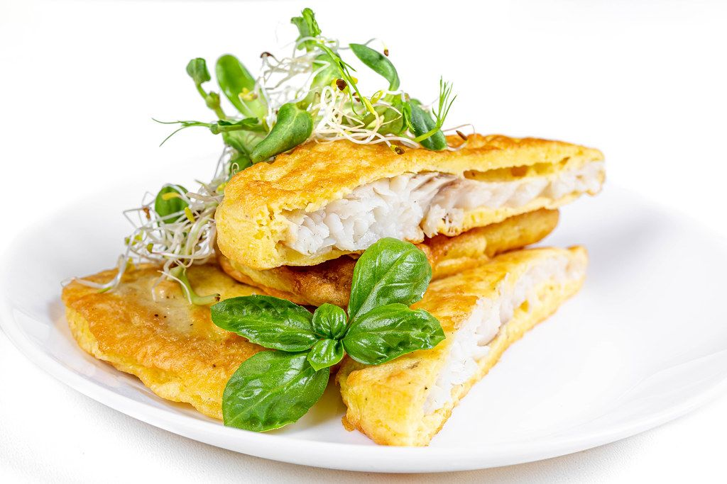 Delicious fried fish in batter with fresh microgreens