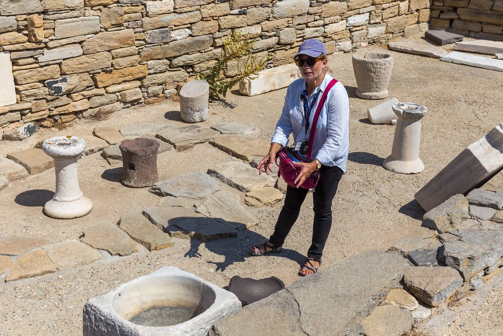 Delos, Greece: tour guide wears transparent shield covering mouth and nose as protection from Covid19