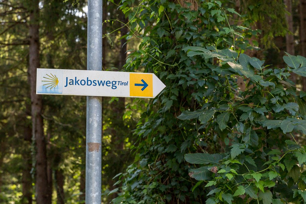 Der gelbe Pfeil des Jakobswegs nach rechts Richtung Tirol