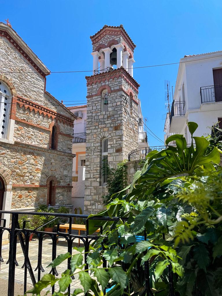 Der Glockenturm der Kirche Agios Georgios von Kyratso mit Steinmauern auf Skopelos, Griechenland
