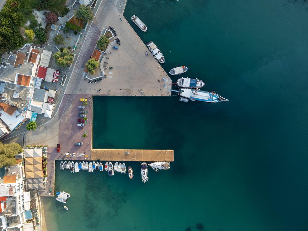 Der Hafen von Patitiri auf Alonnisos: Draufsicht auf das türkise Meer, Boote, Seebrücke und geparkte Autos