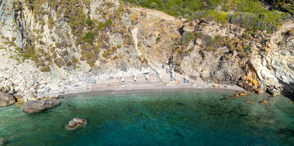 Der schmale Kiesstrand von Agios Ioannis auf Skopelos mit türkisfarbenem Meer, von Felsen umgeben