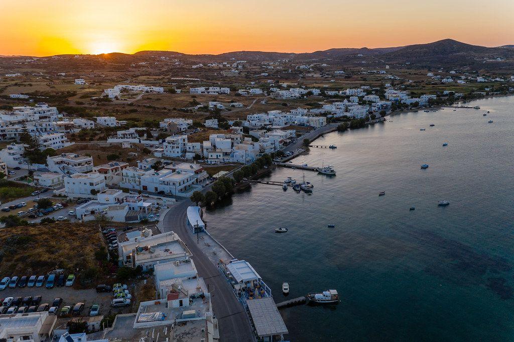 Der Sonnenuntergang in Adamantas, Hafenstadt auf Milos. Luftbild mit weißen Häusern und Booten